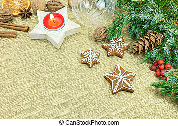 christmas decoration with gingerbread cookies, candle, glass ball and fir tree branches