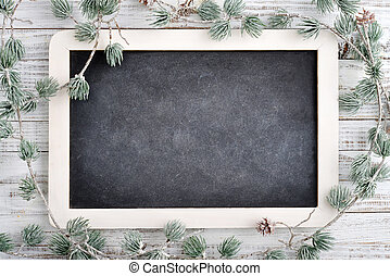 Christmas decorations and slate blackboard on wooden background