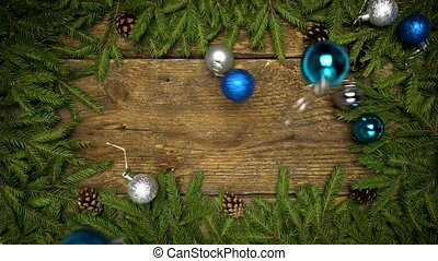 Christmas decorations falling on a wooden background with fir branches and cones ready for your design. Winter holidays background