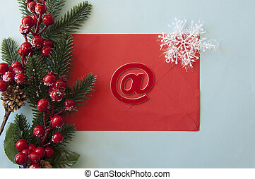 Christmas decorations, fir branches, red envelope, red berries on pastel blue background. Christmas, New Year, winter concept.