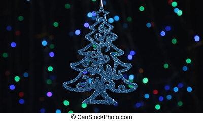 Christmas decorations, herringbone hanging on the background of flashing lights.