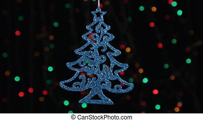 Christmas decorations, herringbone swinging on the background of flashing lights.