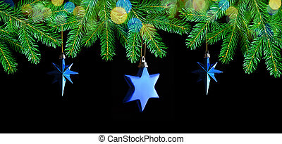 Christmas decorations in the shape star hanging on fir branch.