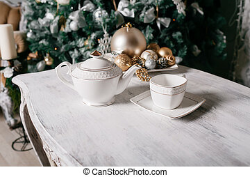 Christmas decorations on the table against the background of a fireplace decorated with branches spruce and garland.