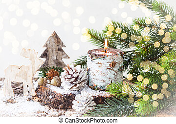 Christmas decorations with burning candle, wooden toys, fir ...