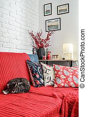 Christmas decorations with candles and red plaid on couch