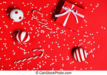 Christmas decorations with candy canes, gift box and christmas toys on red background.