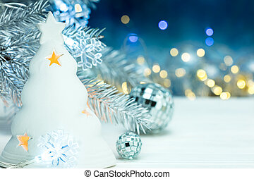 christmas decorations with fir tree branch on blurred lights background
