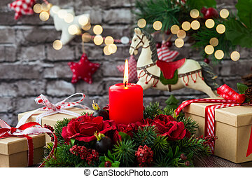 Christmas decorations with red candle, gift boxes and rocking horse on the old wooden table