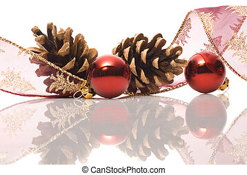 christmas decorations with ribbon, cones and red balls of glass reflected on white background