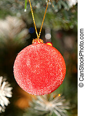 christmas decorative ball with tree and lights in background