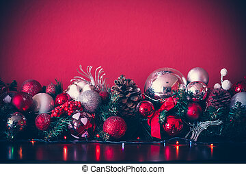 Christmas decorative garland with fir branches, red and silver baubles, pine cones and other ornaments, in the new-year background