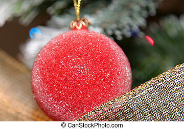 christmas decorative red ball and ribbon with tree in background