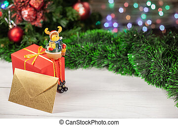 Christmas deer figure sits on a gift that is on a white wooden table next to a green tinsel in the background a colorful garland