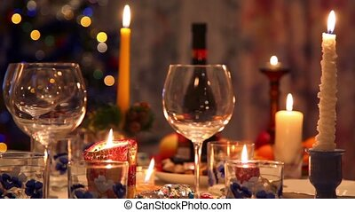 christmas dining table with bottle, glasses, candy, candles