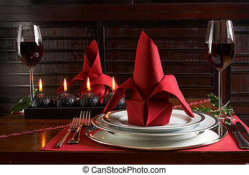 Christmas dinner table with red accents of placemats and...