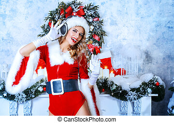 christmas DJ - Beautiful young woman in Santa Claus costume...