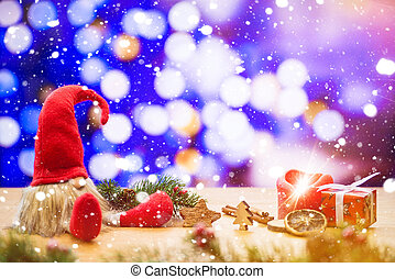 Christmas dwarf in falling snow with bokeh lights in background with ignited advent candle