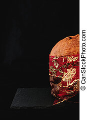 christmas essence, panettone with red ribbon on black background, vertical