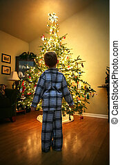 Christmas Eve - a young boy in his pajamas stands in front ...