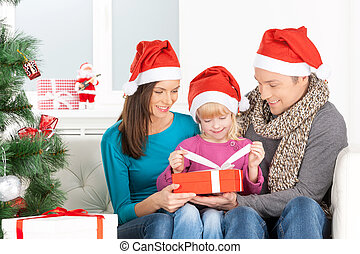 Christmas Eve. Cheerful family opening Christmas gift box and smiling