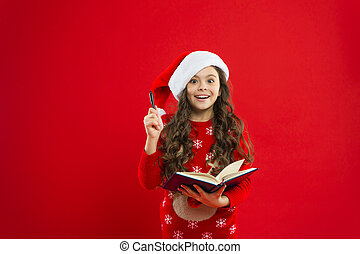 Christmas eve reading. Christmas shopping. Happy winter holidays. Small girl. Little girl child in santa red hat. Present for Xmas. Childhood. New year party. Santa claus kid. Beat the Christmas rush