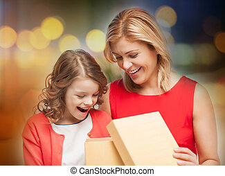happy mother and daughter with gift box