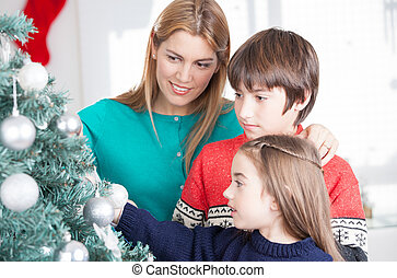 Christmas family concept. Mother with two children decorating tr