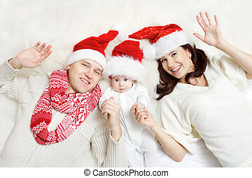 Christmas family of three persons in red hats. Hapy parents and small funny baby