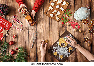 Merry Christmas and Happy Holidays! Mother and daughter prepare Xmas cookies. Baubles, presents, candy and cookies with christmas ornaments. Top view. Christmas family traditions.