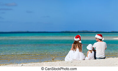 Christmas family vacation - Parents in Santa hats and their...