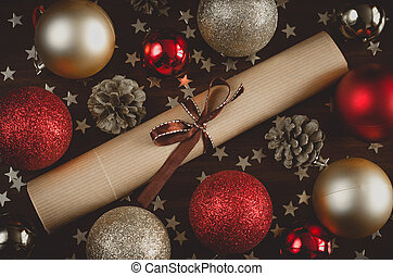 Christmas festive decor, red, gold balls, a letter with a ribbon, a cone on the table flat lay top view