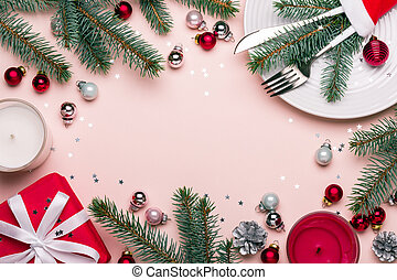 Christmas festive frame with Christmas decorations in red, pink and green colors. Celebration table setting.