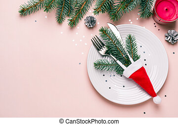 Christmas festive table setting. Fir branches and cutlery in Santa hat on pink background