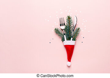 Christmas festive table setting. Fir branches and cutlery in Santa hat
