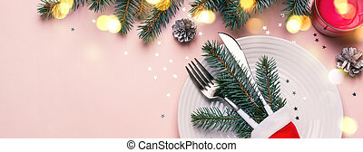 Christmas festive table setting. Fir branches, bokeh lights and cutlery in Santa hat on pink background