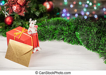 Christmas figure of a deer sitting on a gift next to an envelope that is on a white wooden table next to a green tinsel in the background colorful garland