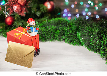 Christmas figure of a snowman sitting on a gift next to an envelope that is on a white wooden table next to a green tinsel in the background colorful garland