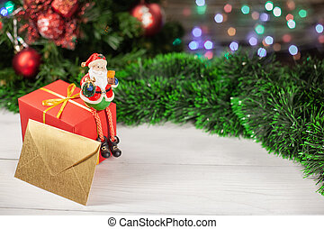 Christmas figure of Santa Claus sitting on a gift next to an envelope that is on a white wooden table next to a green tinsel in the background colorful garland