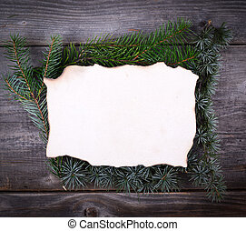 Christmas Fir Tree Border over blank paper on wooden background