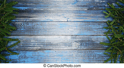 christmas fir tree branches frame om old blue wooden background