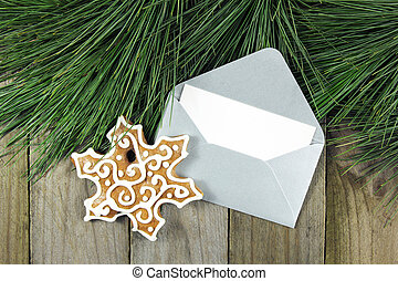 christmas fir tree, silver envelope with gingerbread on wooden b