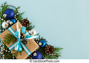 Christmas flat lay composition of fir branches with gift box and decorations at the left bottom corner with copy space on the blue background.
