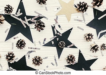christmas flat lay. modern christmas layout with golden pine cones, silver confetti, black stars on white wood, top view. holiday greeting card. stylish winter flatlay. pattern