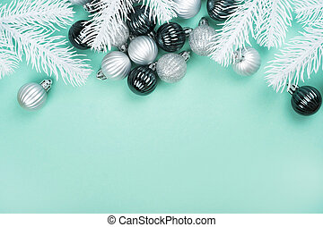 Christmas flatlay with silver baubles and white pine tree branches isolated on mint green background. New Year concept.