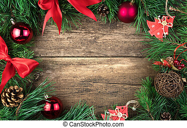 Christmas frame decorated with red Christmas toys, bows and glass balls pine branch on a natural wooden background.