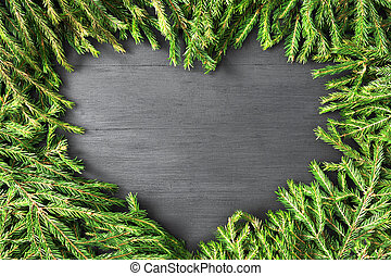 Christmas frame heart shaped made of natural fir branches on black wooden background. Flat lay, top view