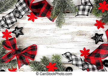 Christmas frame of ornaments, branches and checked buffalo plaid ribbon. Top view on a rustic white wood background.