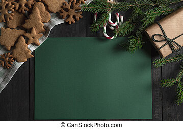 Christmas frame with cookies candy canes and gift. Blank paper note. Top view. Copy space.