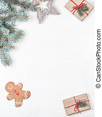 Christmas frame with gifts, fir tree branches, xmas holiday decorations, festive symbols on white wooden background with copyspace. Christmas composition.